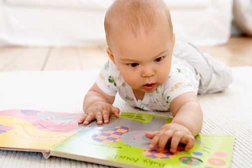 Baby boy lying on floor with picture book, touching page with his hands, front view
